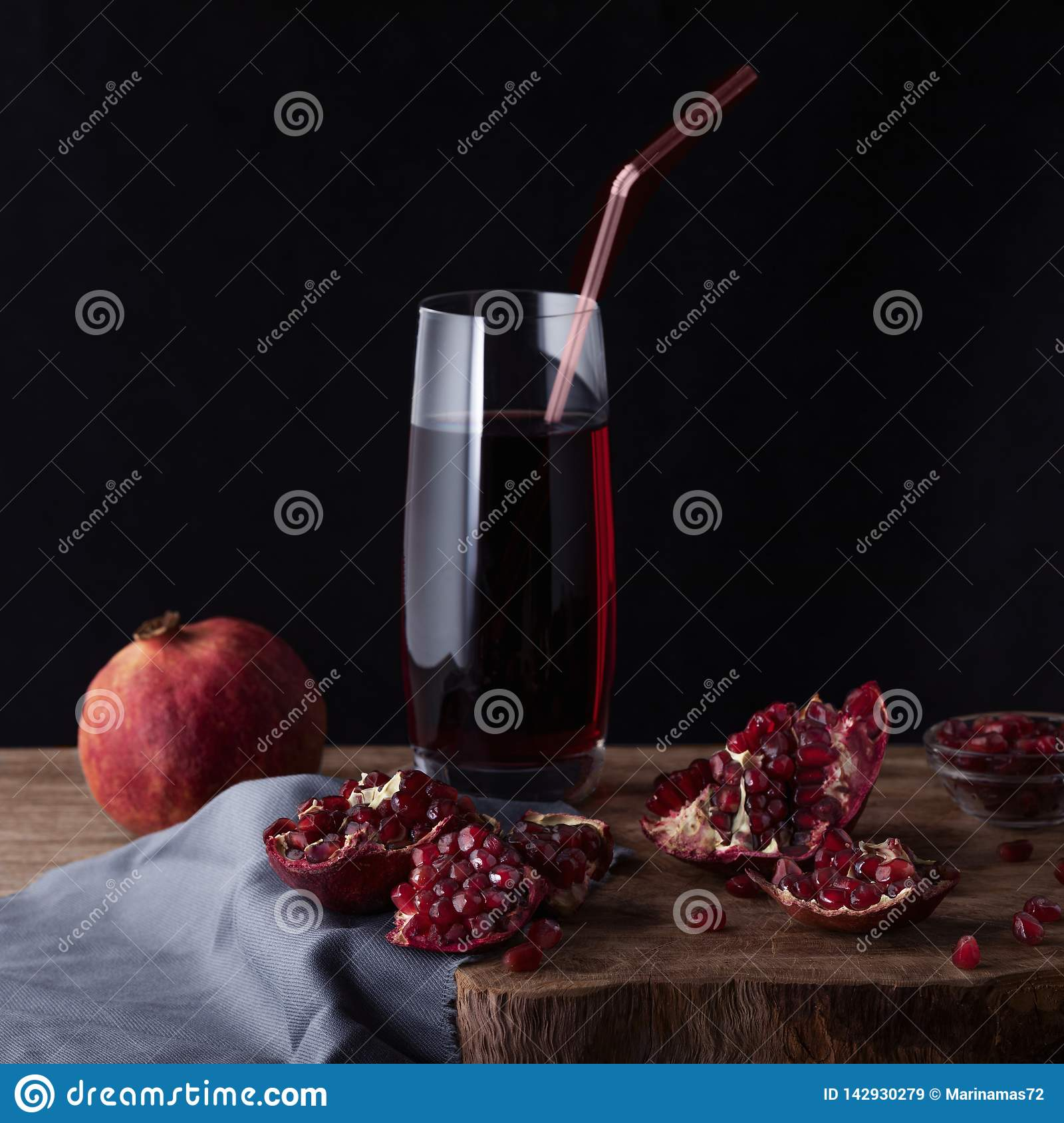 Glass of pomegranate juice with pomegranate slices and garnet fruit