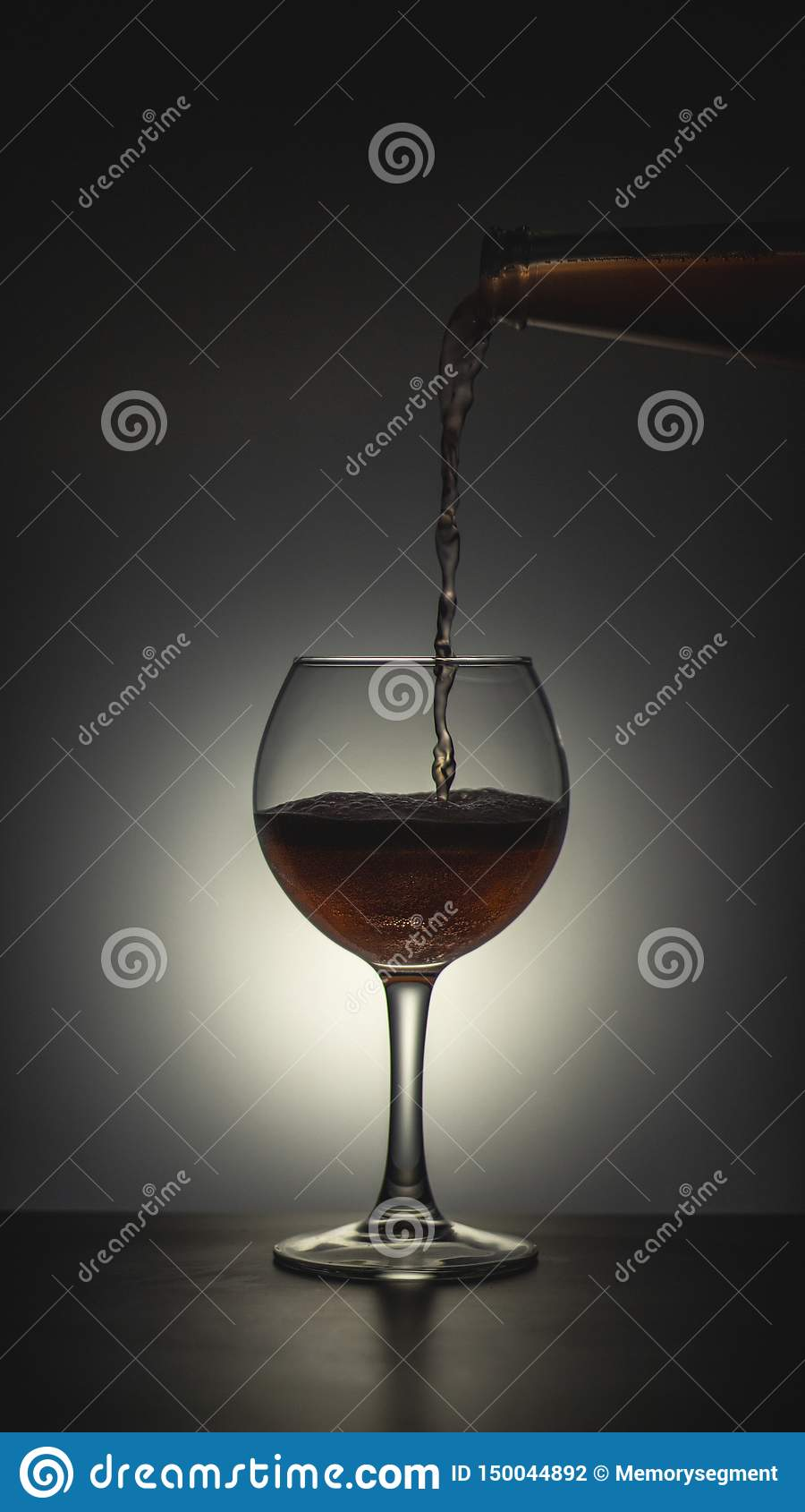 A glass that poured alcohol on a dark background