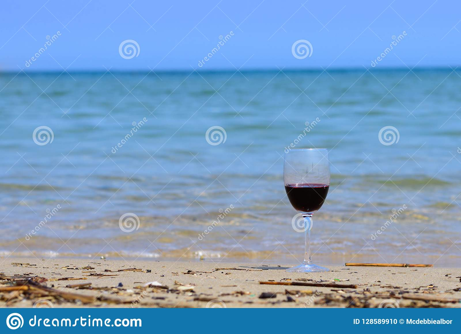 A glass of red wine on the beach seashore in summer on sunny day with blue sea.