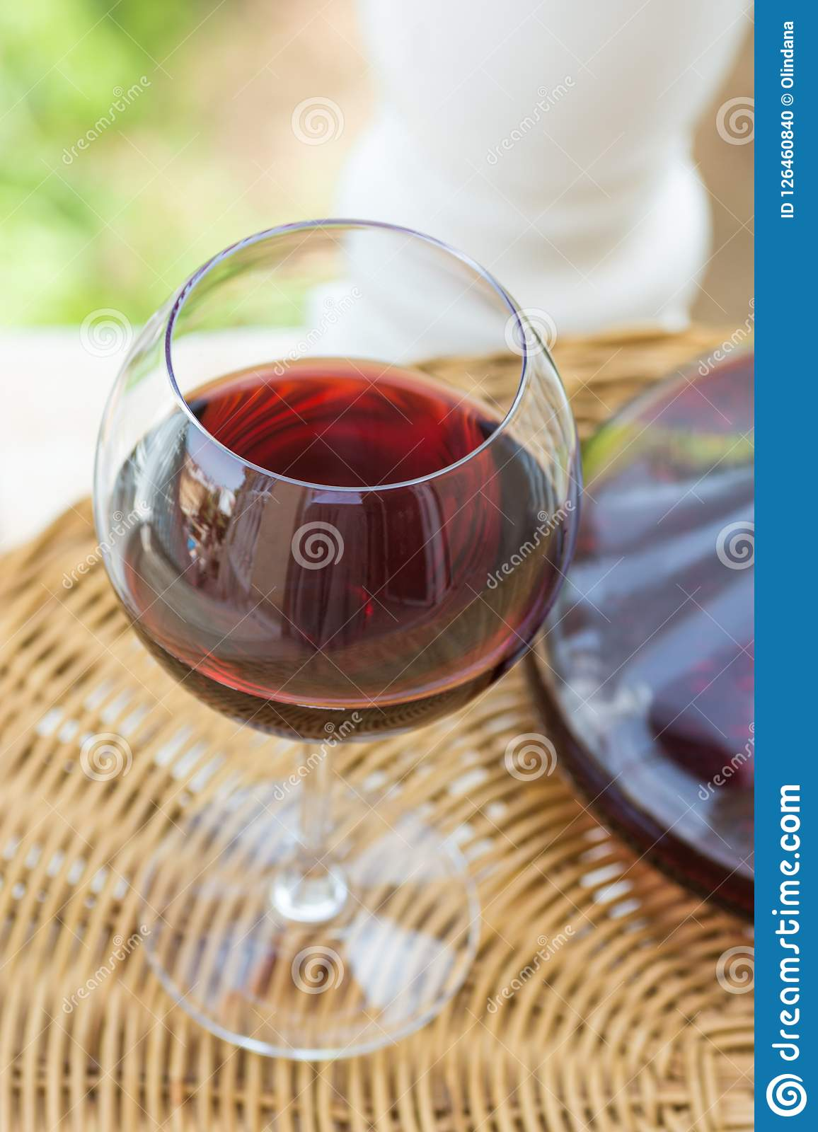 Glass with Red Wine and Crystal Decanter on Wicker Table in Garden Terrace of Luxurious Villa or Mansion. Authentic Lifestyle