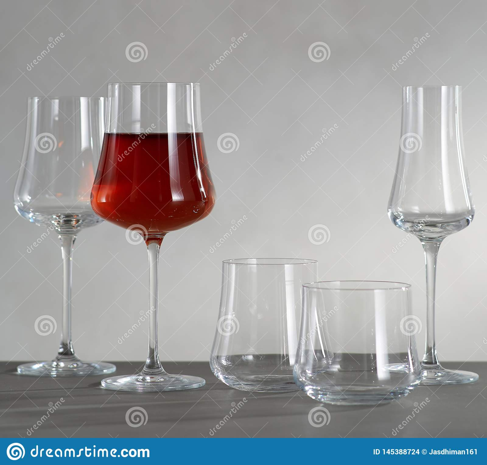 A glass of red wine and four empty wine glasses