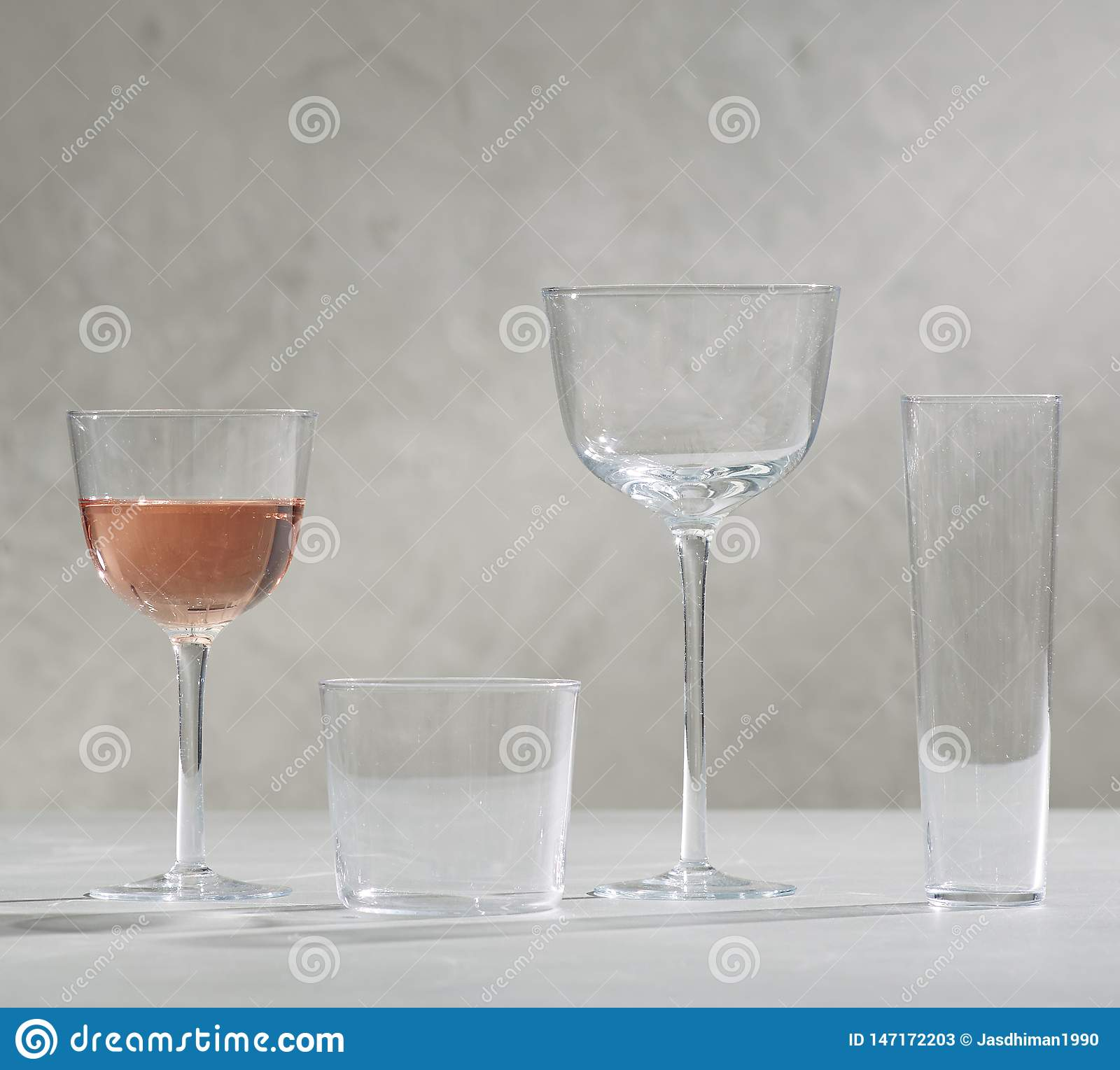A glass of red wine and four empty wine glasses, A glass of red wine and four empty wine glasses