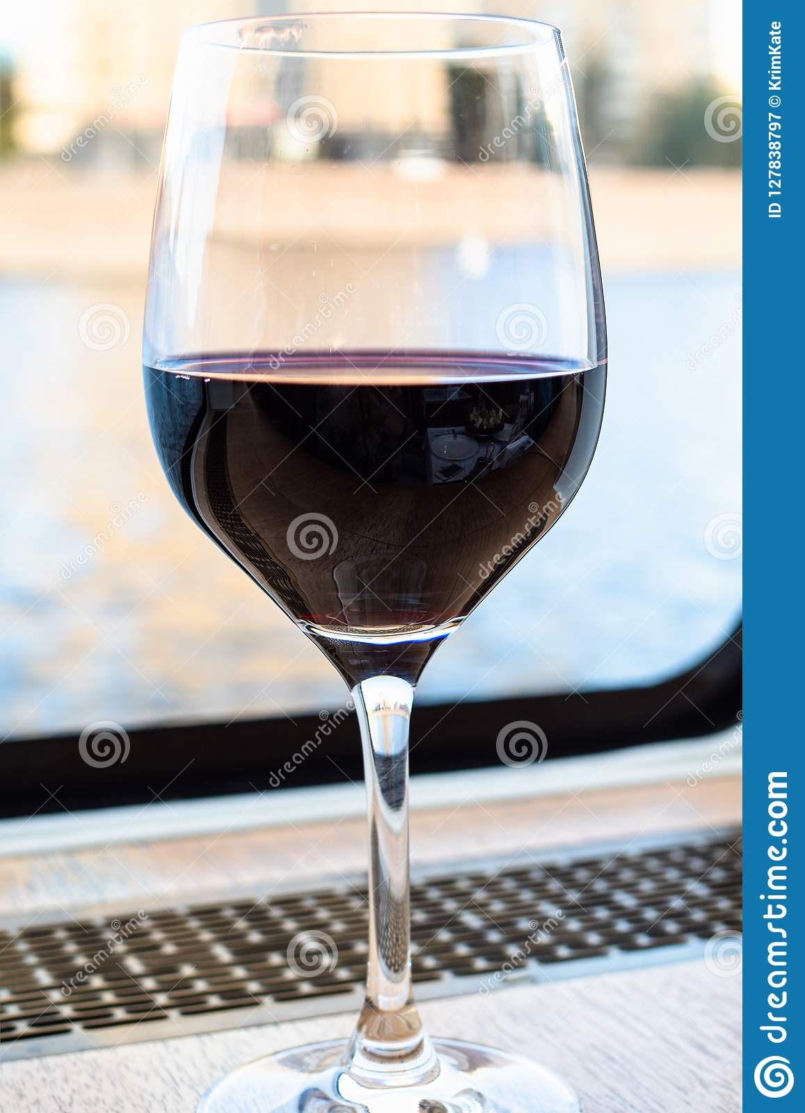 Glass of red wine near window of cruise ship