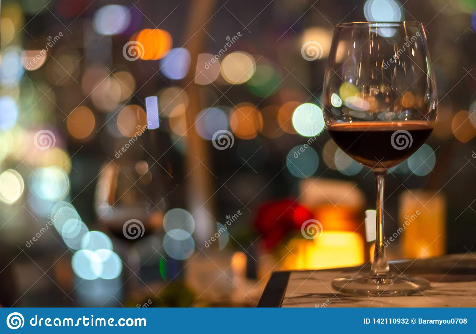 A glass of red wine on table of rooftop bar