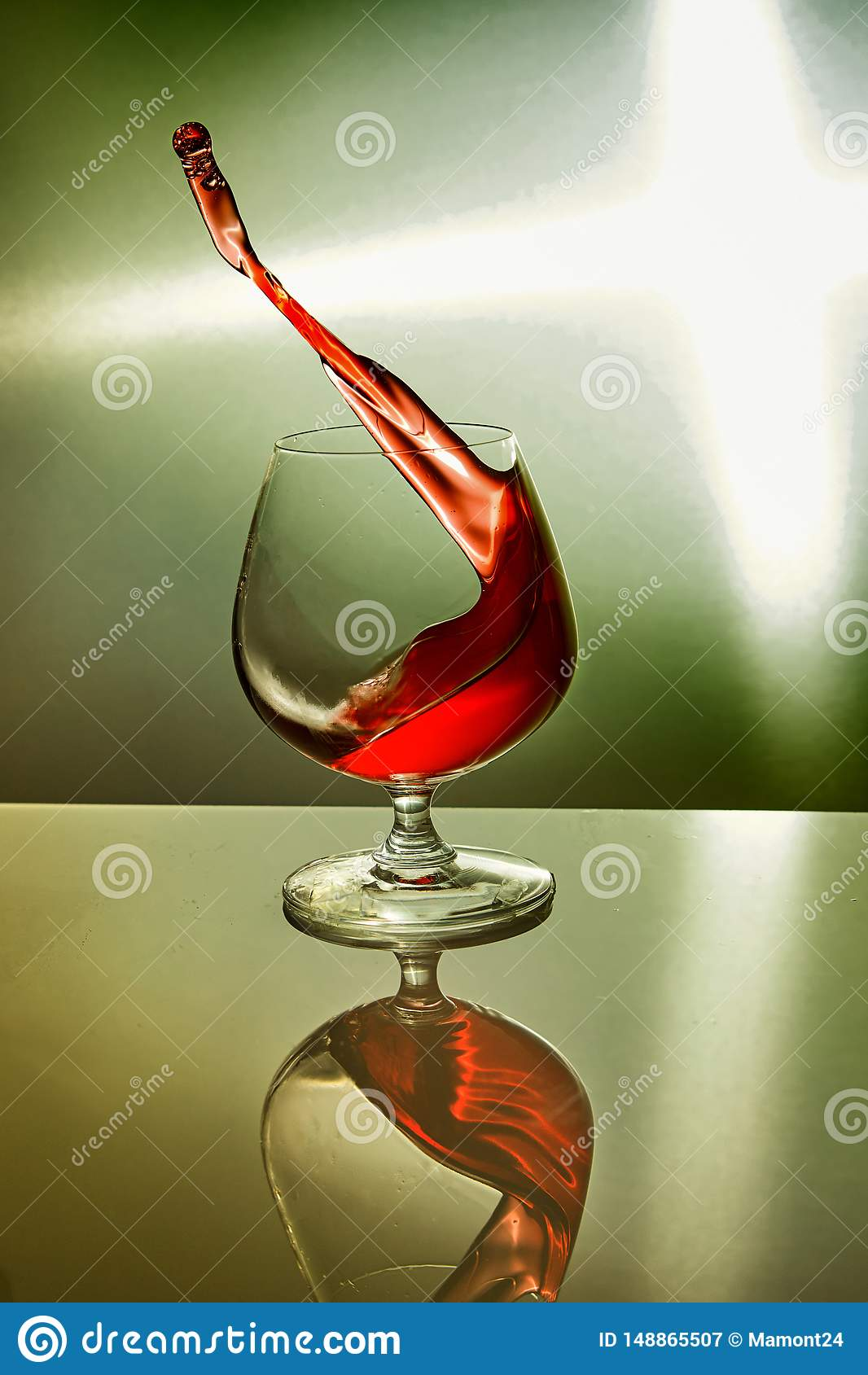 Glass of red wine with wave on green background