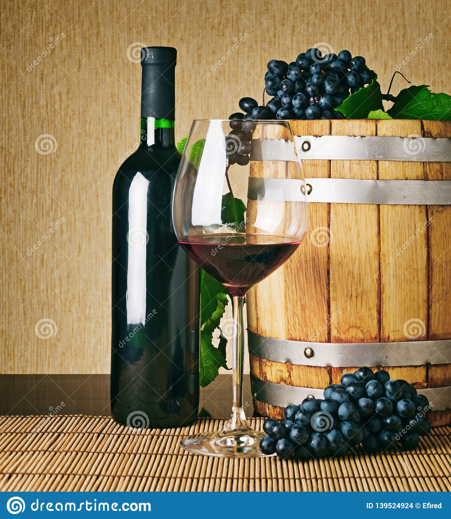 Glass of red wine, wine bottle and wooden barrel
