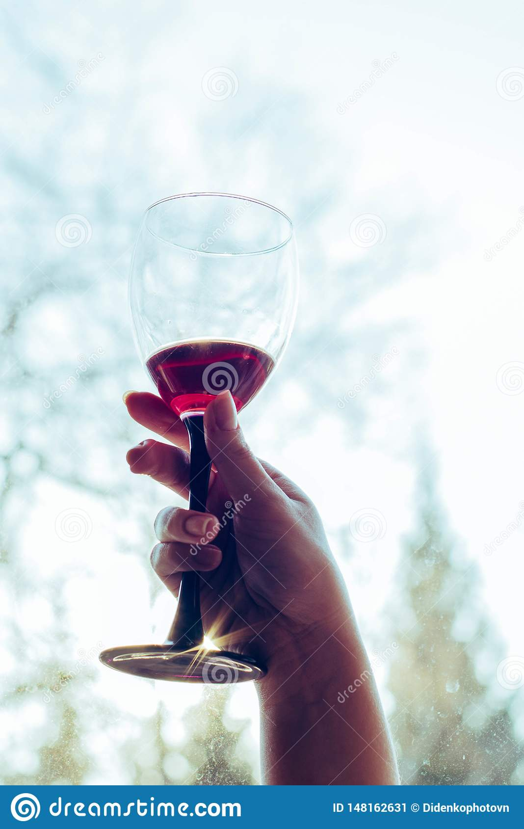 A glass of red wine in the hands of a girl