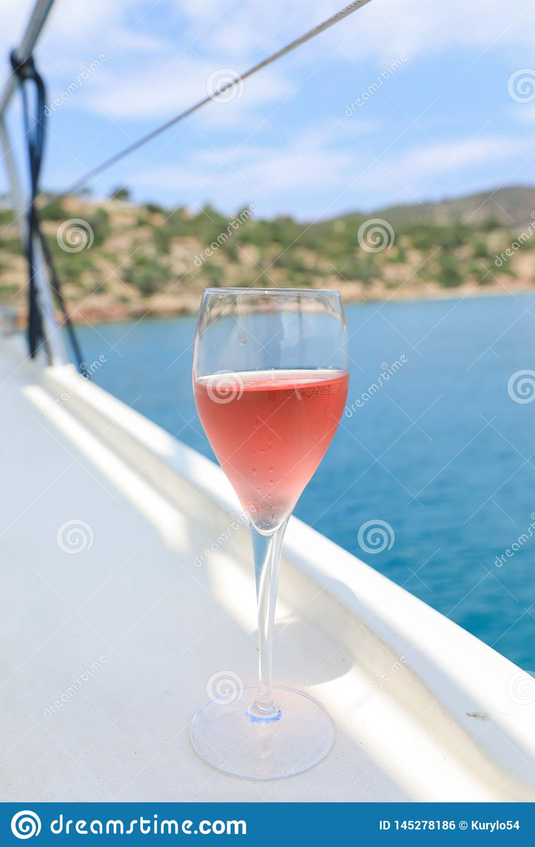 A glass of rose wine on the deck for the beginning of a summer holiday on a yacht in the Aegean Sea