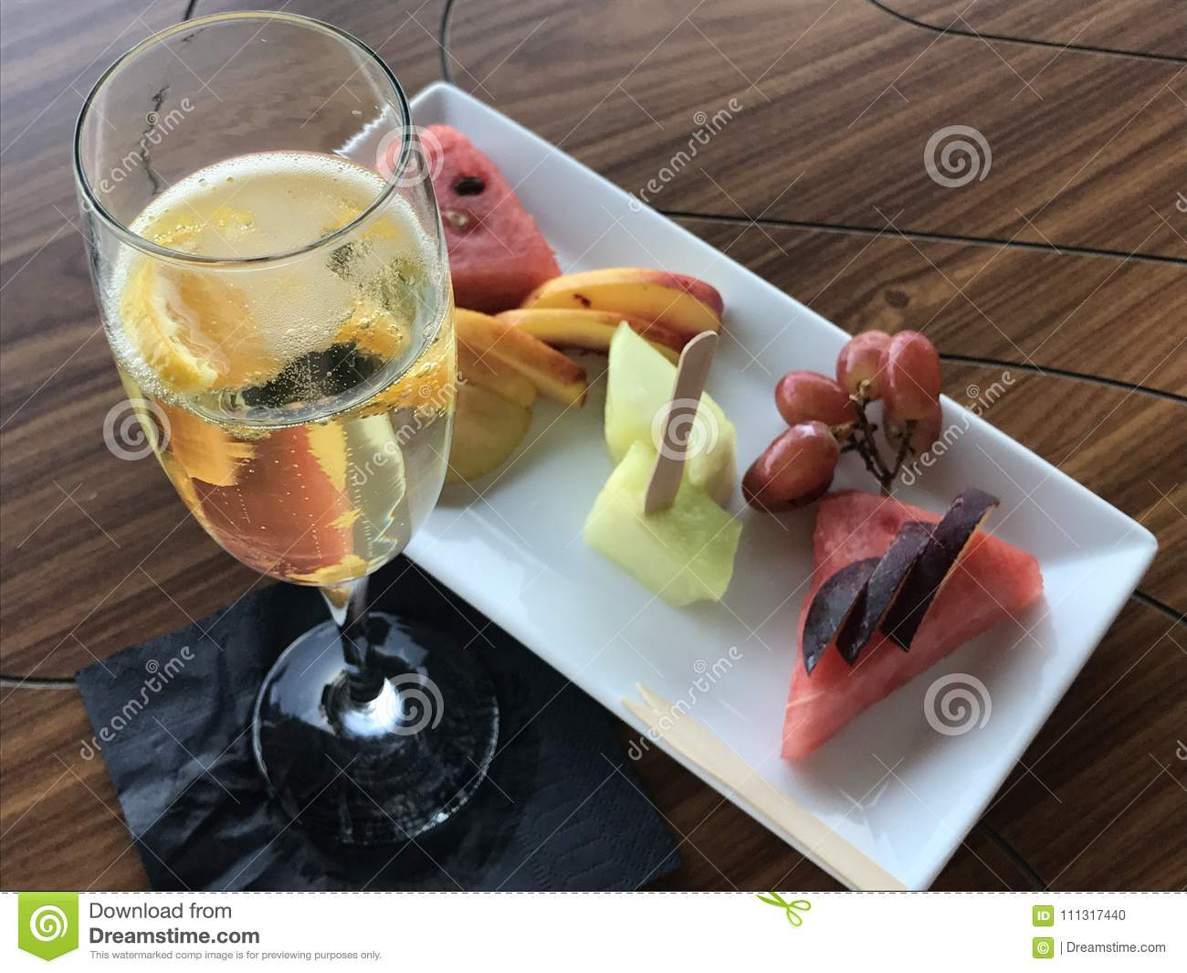 A glass of sparkling wine and fruit salad.