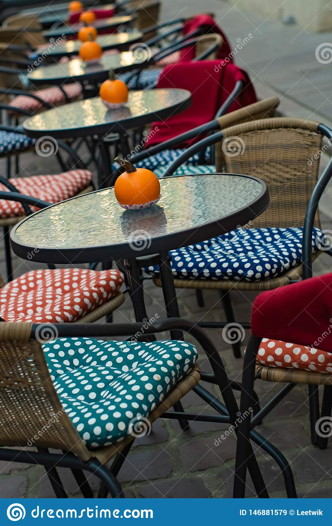 Glass tables of an outdoor cafe with pumpkins and colored cushions of chairs