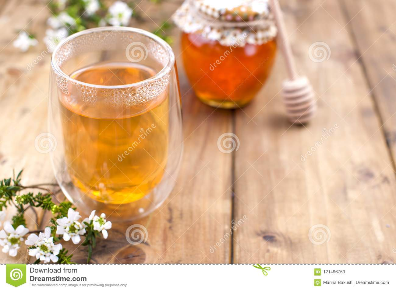 A Glass With Tea Spring White Flowers Bank With Honey Dried Tea