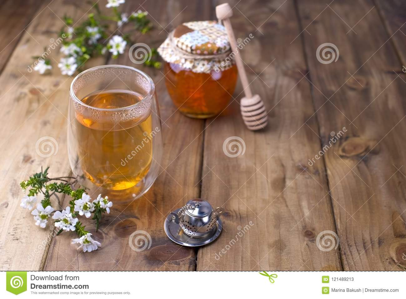 A Glass With Tea Spring White Flowers Bank With Honey Wooden