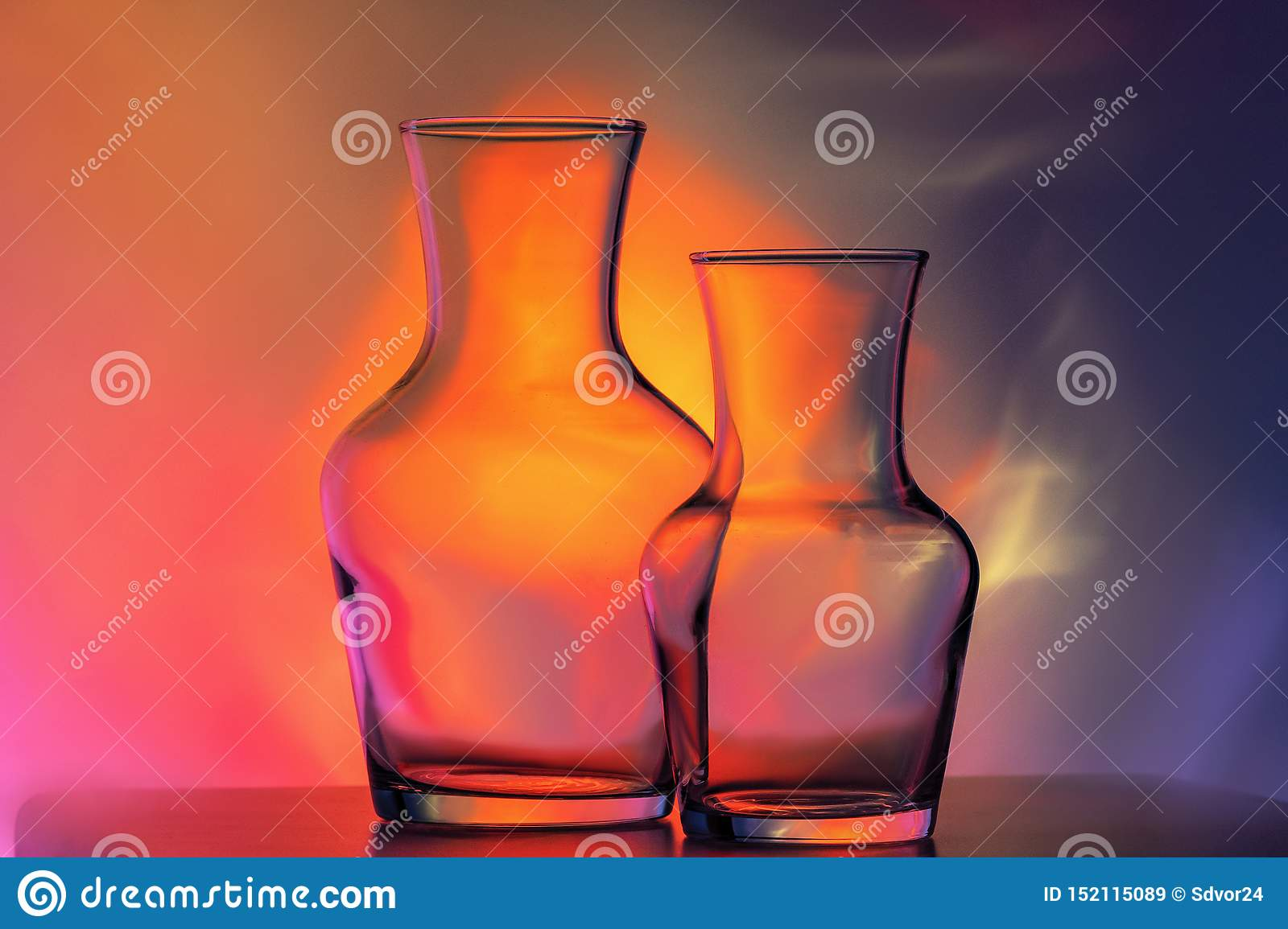 Glass transparent tableware - bottles of different sizes, three pieces on a beautiful multi-colored, yellow, lilac and