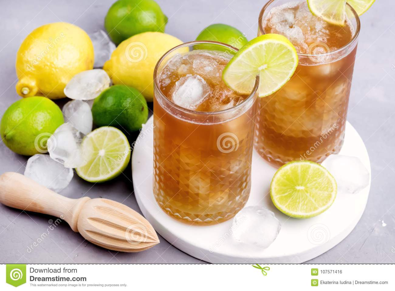Glass of Tsasty Ice Tea with Ice Cubes and Citrus Cold Summ er Beverage Wooden Squeezer and Raw Lemons and Limes on Background