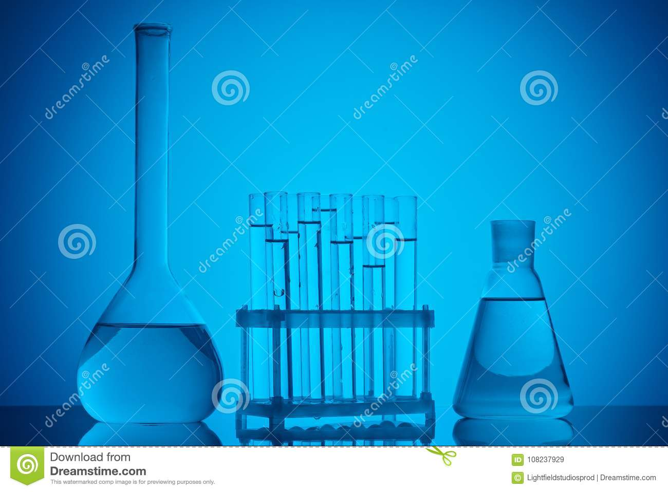 Glass tubes on stand and glass flasks with liquid on table