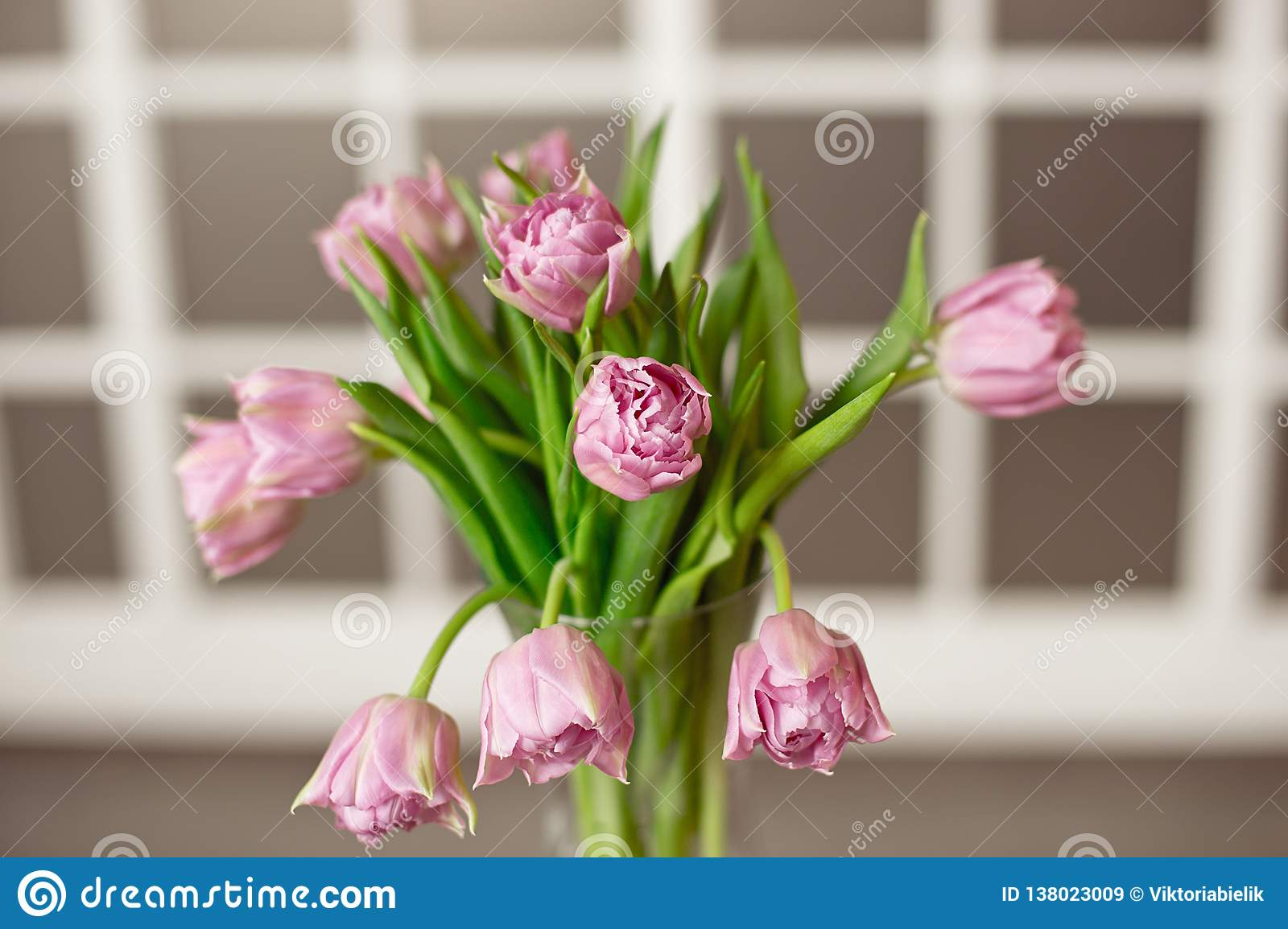 Glass vase with a bouquet of beautiful purple tulips against the background of a stained glass window.