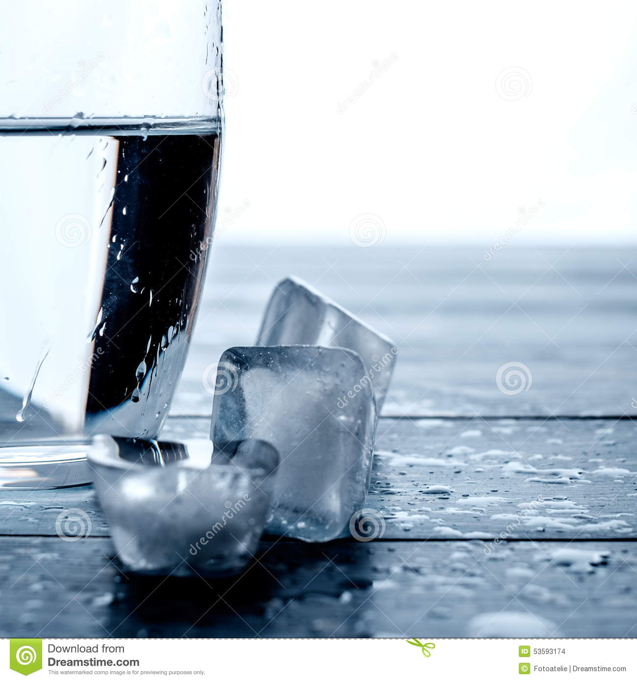 Glass Of Water And Melting Ice Cubes On A Wooden Table ...