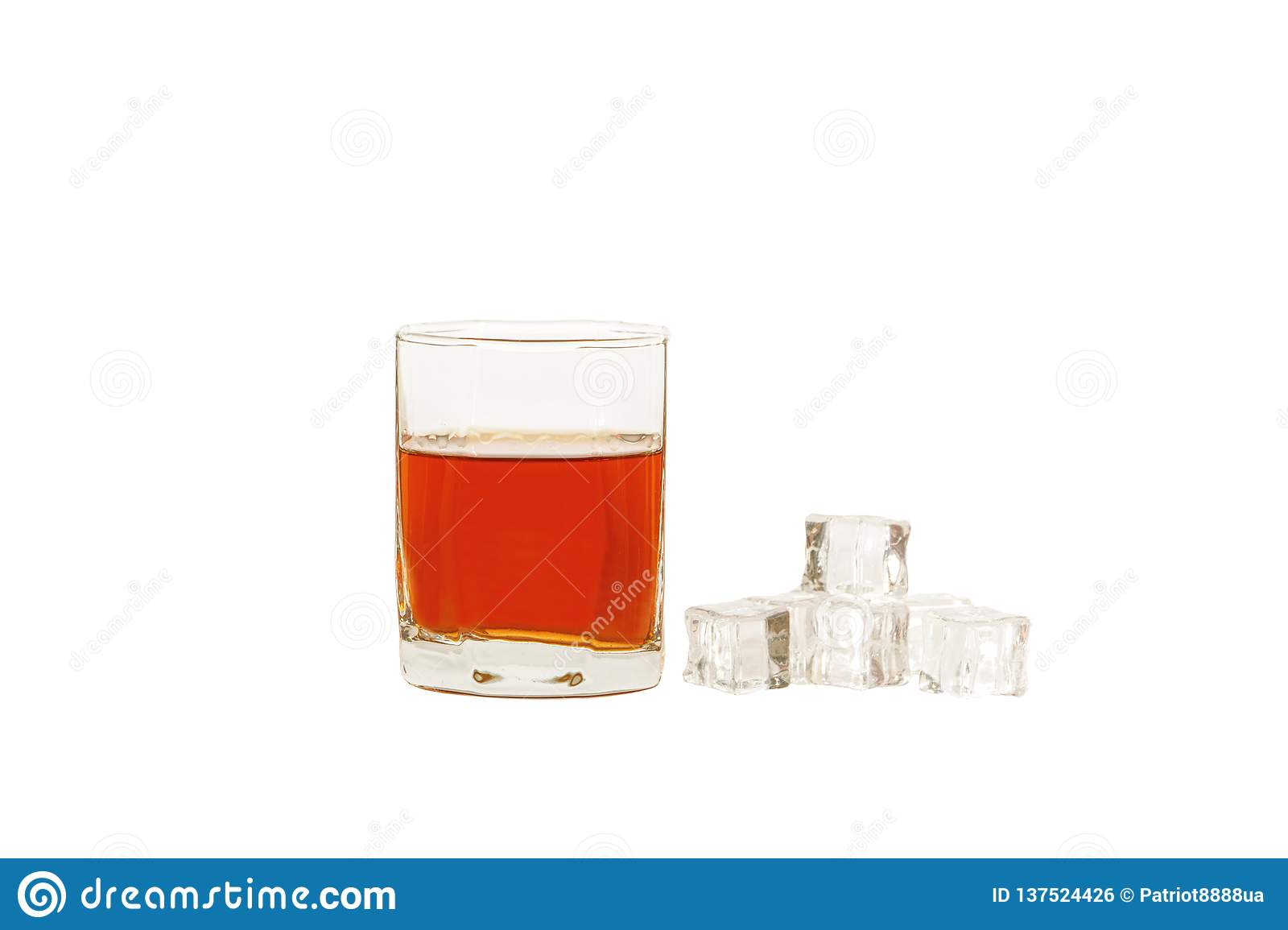 A glass of whiskey with ice or brandy and a square carafe isolated on a white background. Whiskey with ice in a glass a