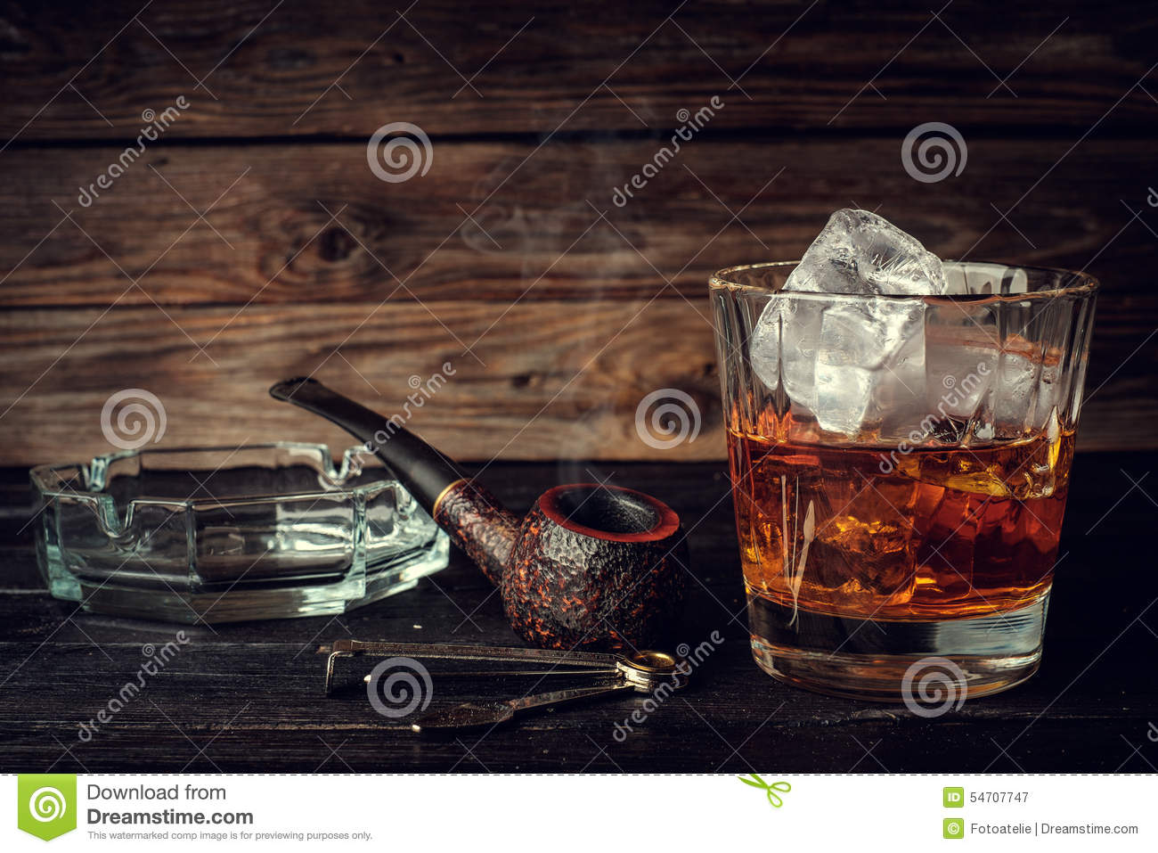 Glass Of Whiskey With Ice And Pipe On A Wooden Background  Stock
