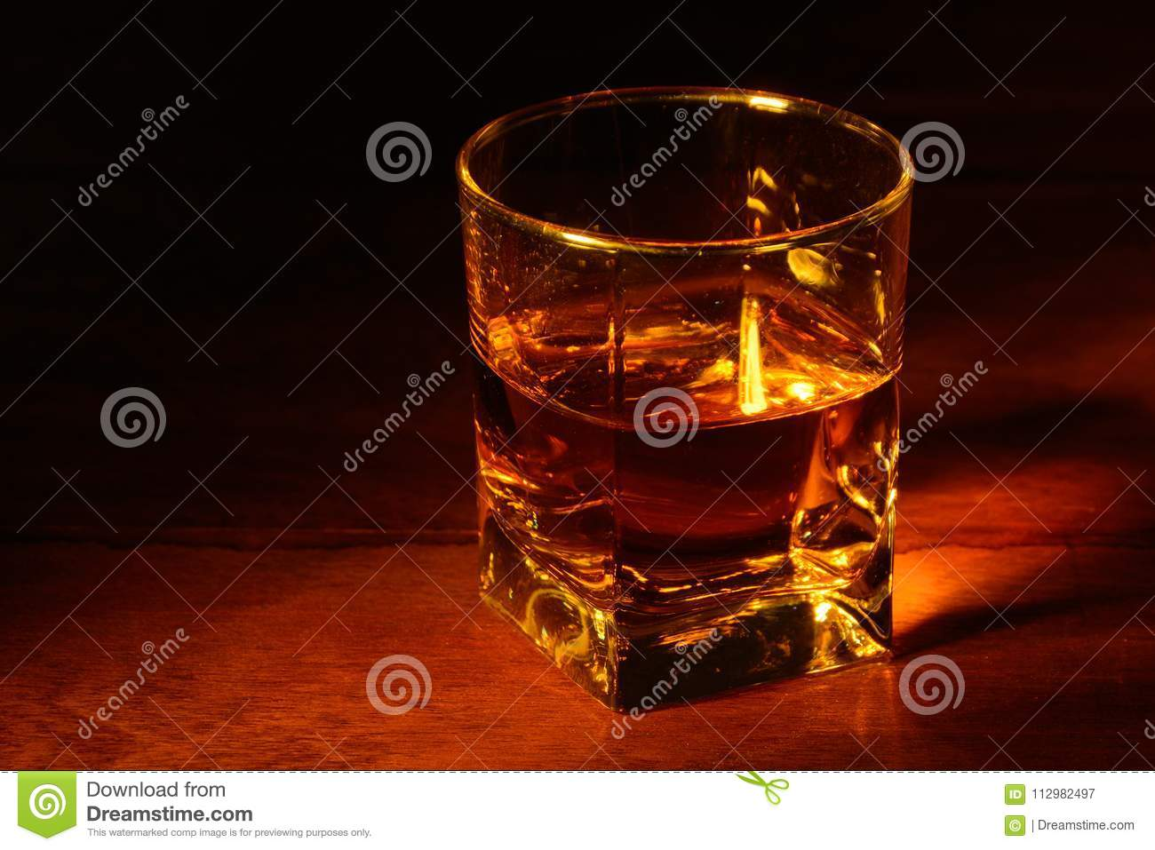 A glass of whiskey on a wooden table and a dark background