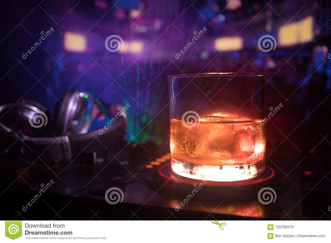 Glass with whisky with ice cube inside on dj controller at nightclub. Dj Console with club drink at music party in nightclub with