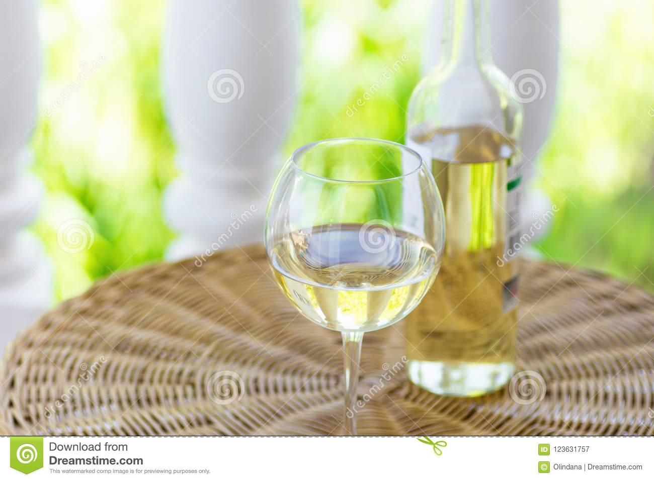 Glass of white dry wine and bottle on wicker table on garden terrace of villa or mansion. Authentic lifestyle image.