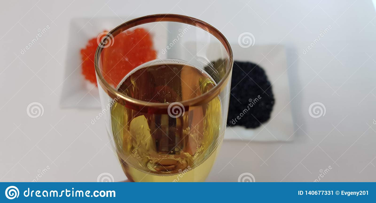 Glass of white sparkling wine against black and red caviar