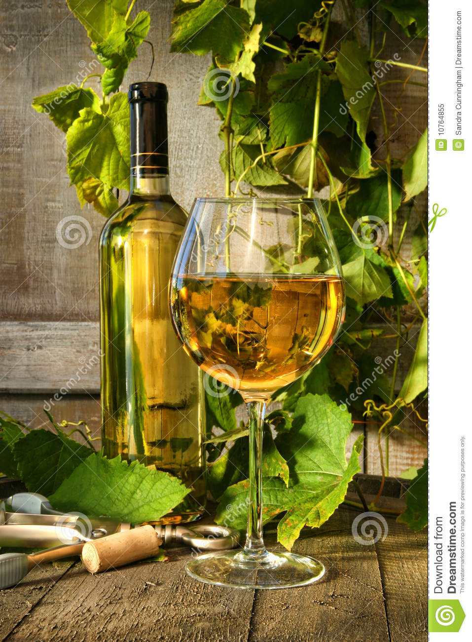 Glass of white wine and bottle on barrel
