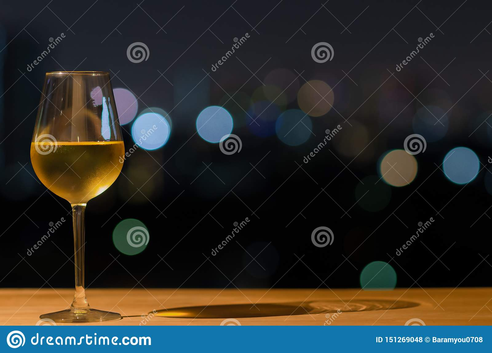 A glass of white wine and its shadow on wooden table of rooftop bar with colorful bokeh of city light and space for text