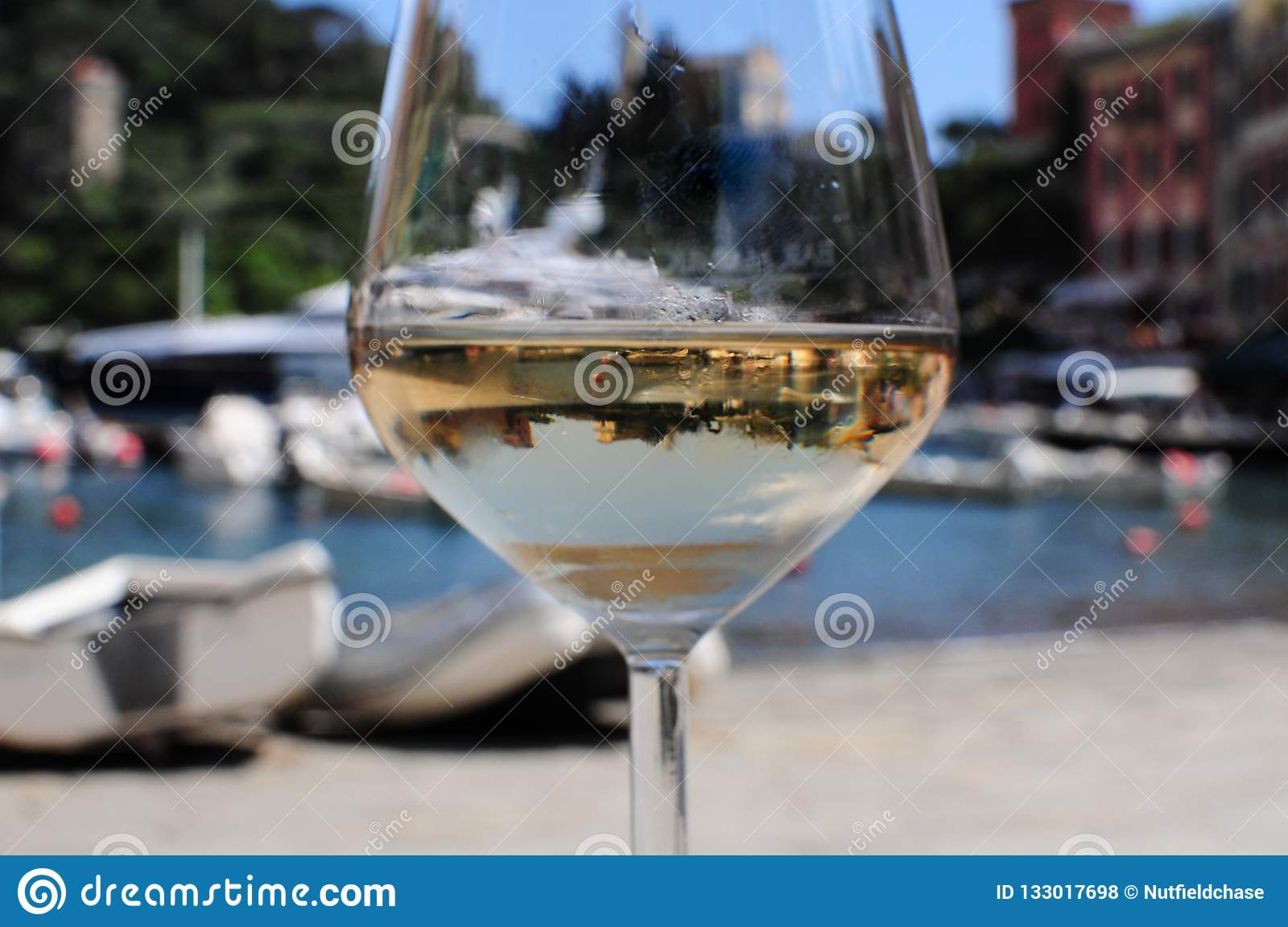 A Glass Of White Wine At Portofino With A Reflection Of The