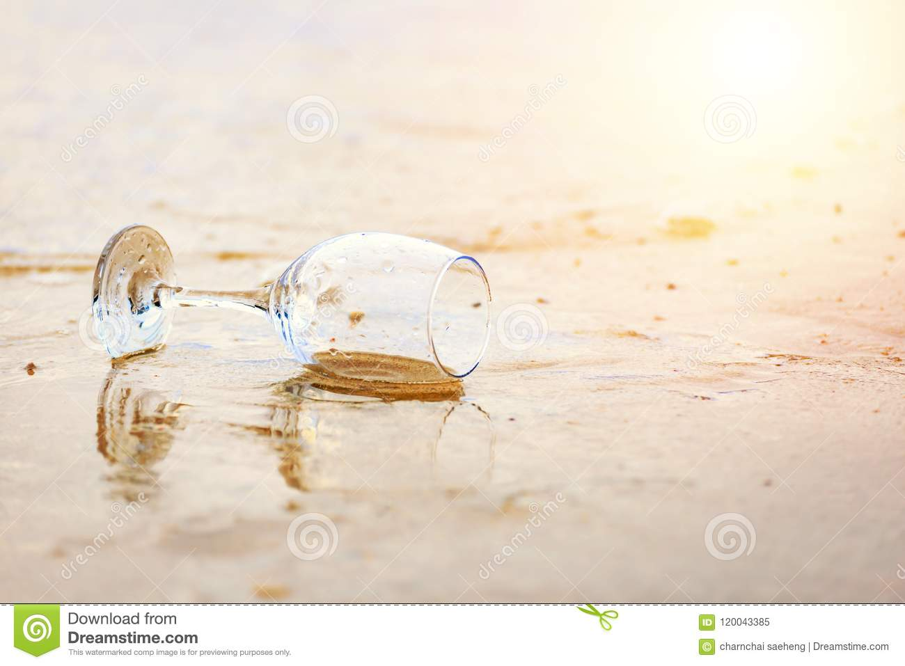 Glass wine on the beach and sea water flow in golden hour