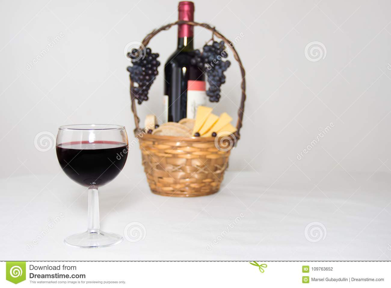 A glass of wine. A bottle of red wine, grapes and picnic basket with cheese slices on white background.