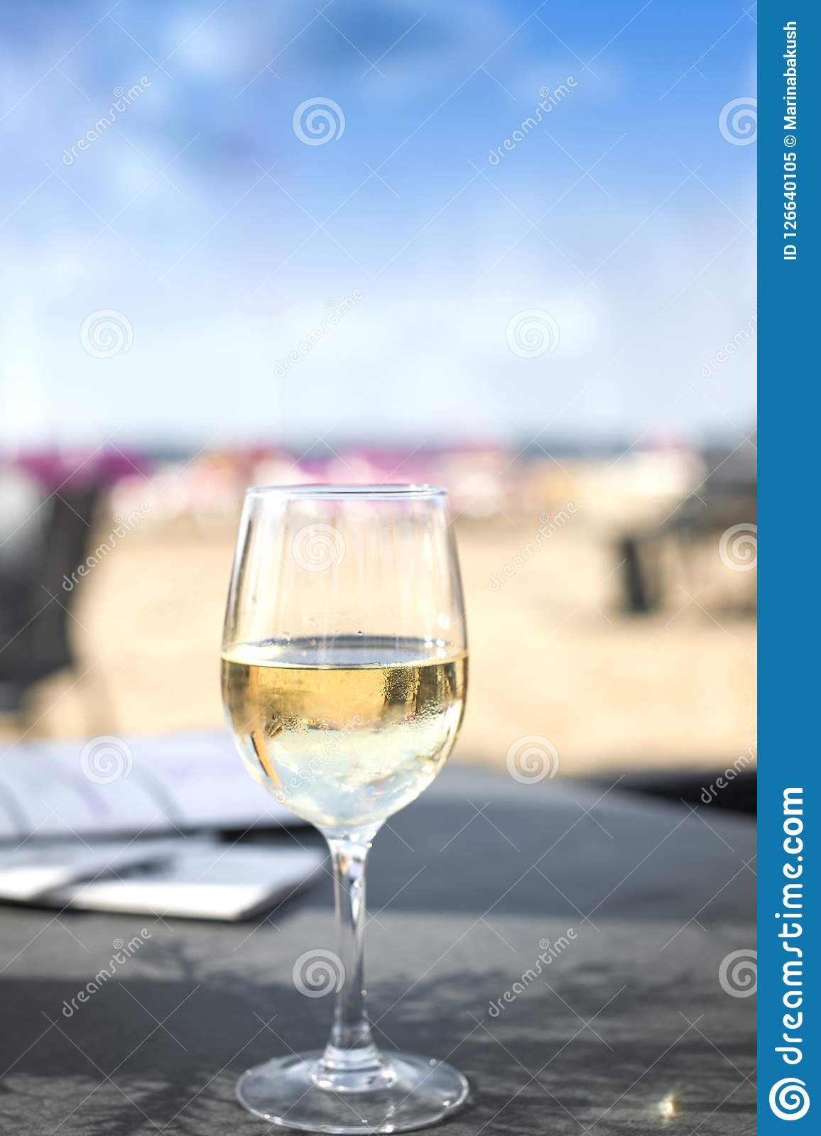 A glass of wine in a cafe on the beach. Romance and the sea.