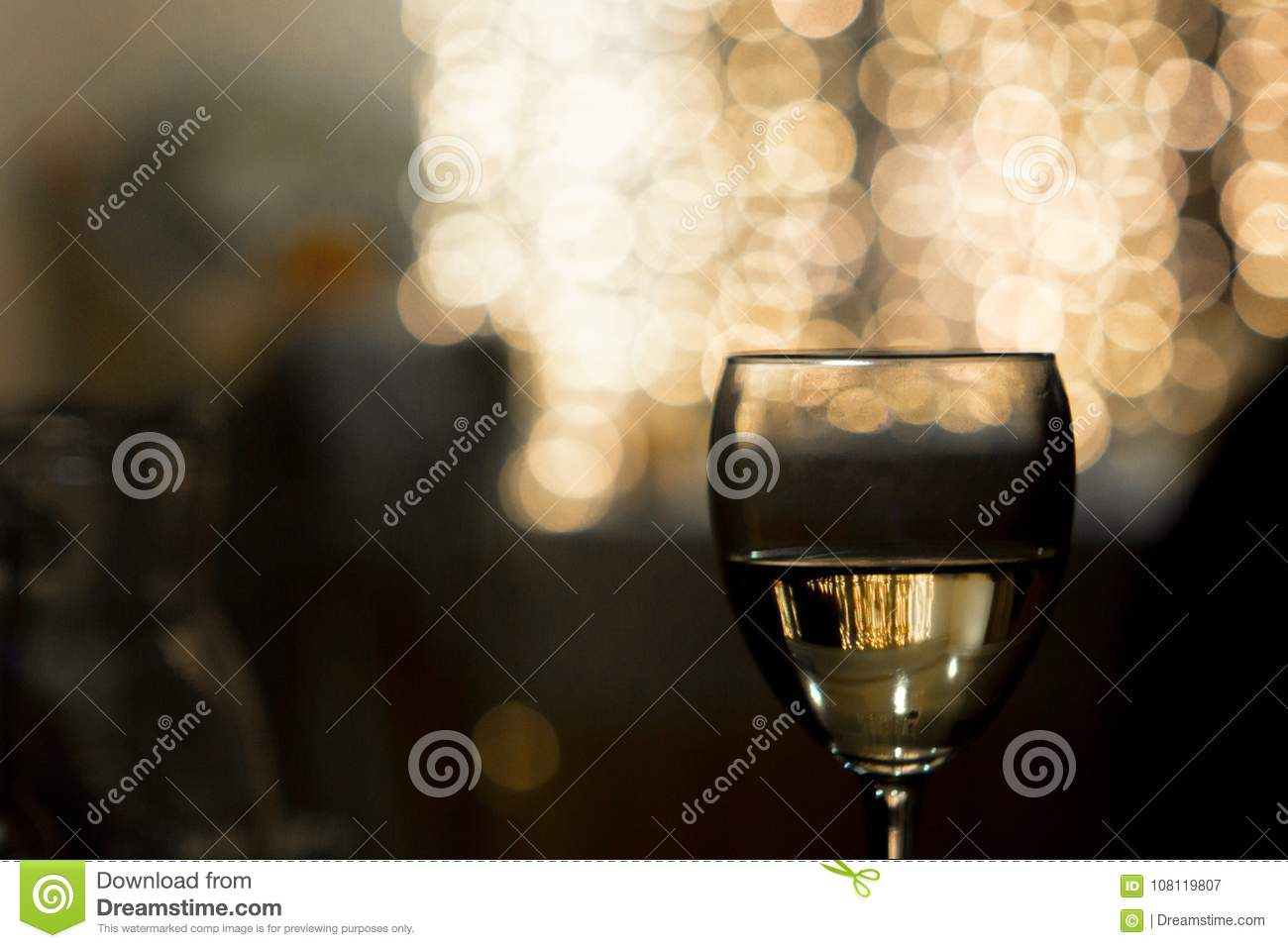 A glass of wine on a lighted background