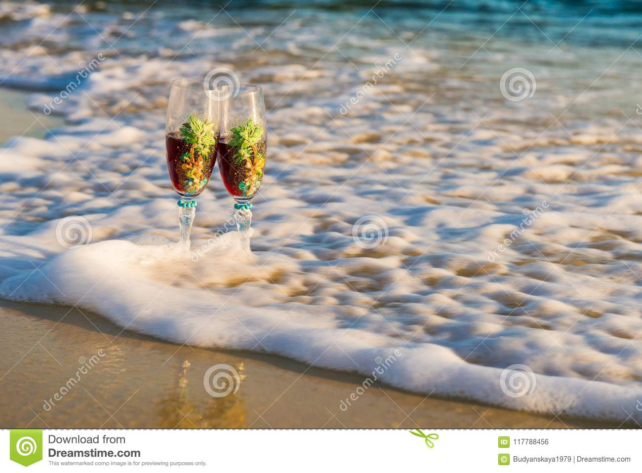 Glass of wine in the rays of the sunset. Glass on the sand