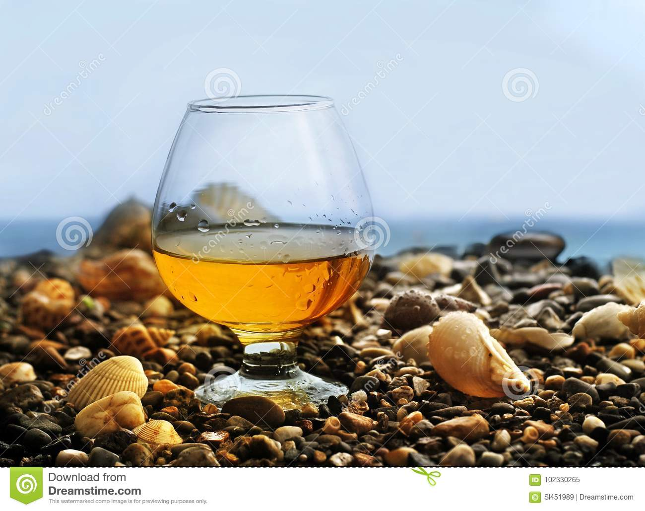 A glass of wine on the stones on the beach