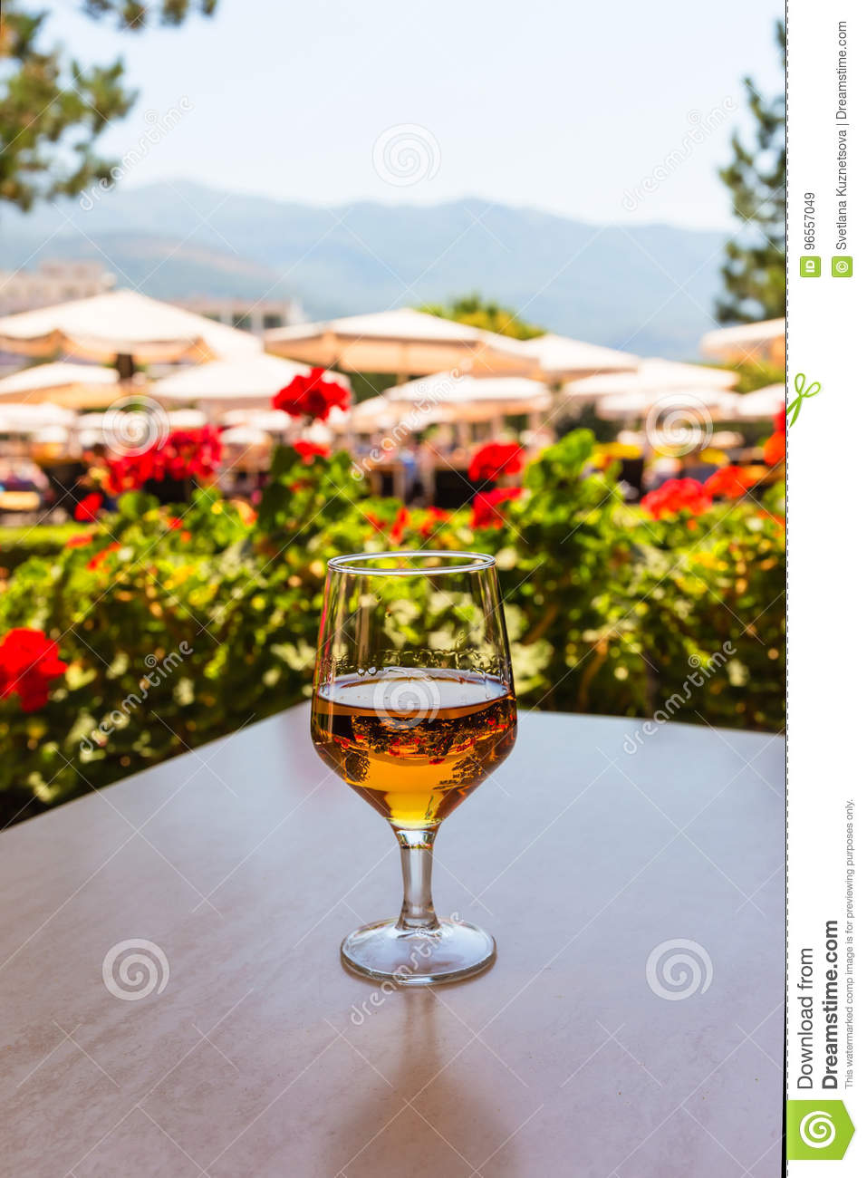 glass of wine on wooden table in the background of beach umbrellas