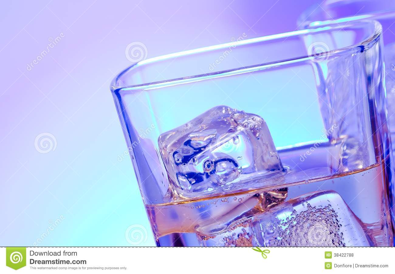 Glasses of alcoholic drink cocktail with ice on disco blue light