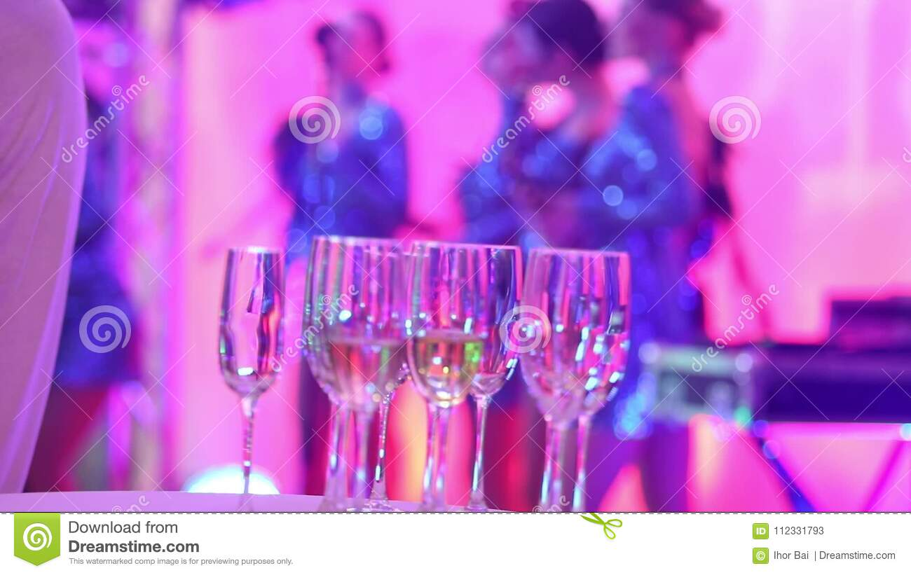Glasses with champagne on the background of silhouettes of women`s music  group, a female music band performs in