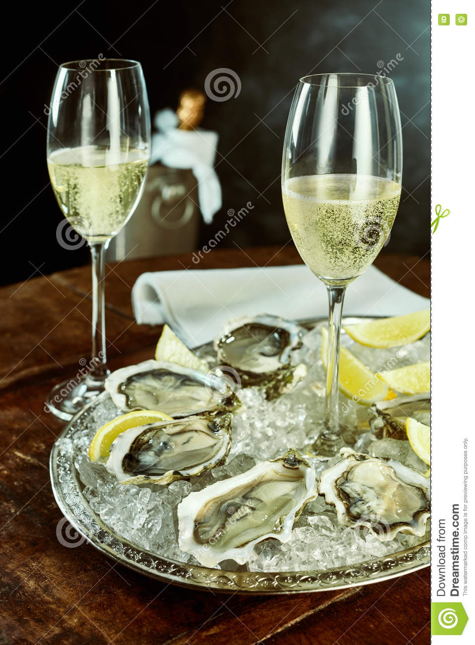 Glasses of champagne and oysters on table