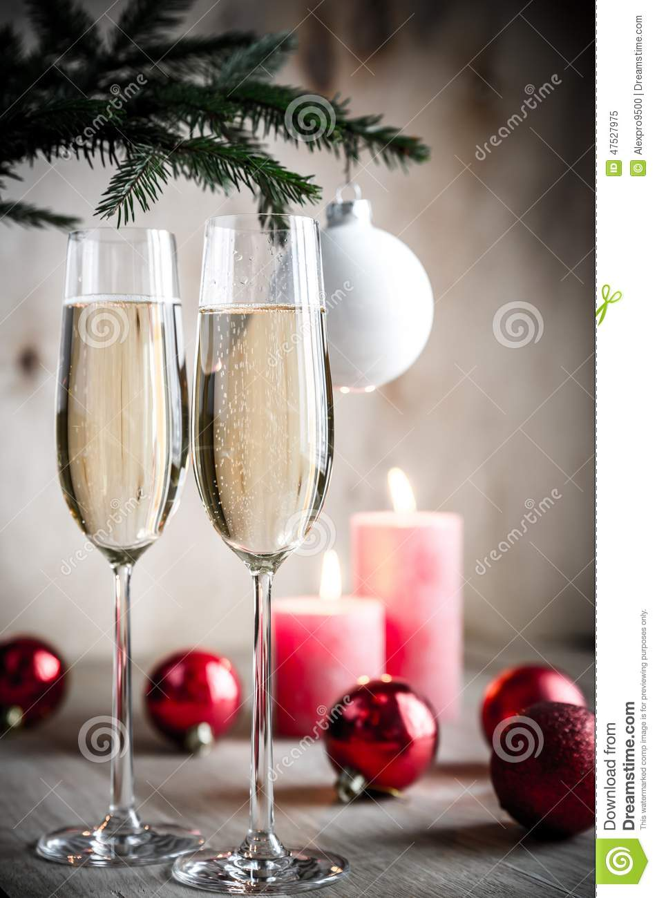 Glasses of champagne under decorated christmas tree branch