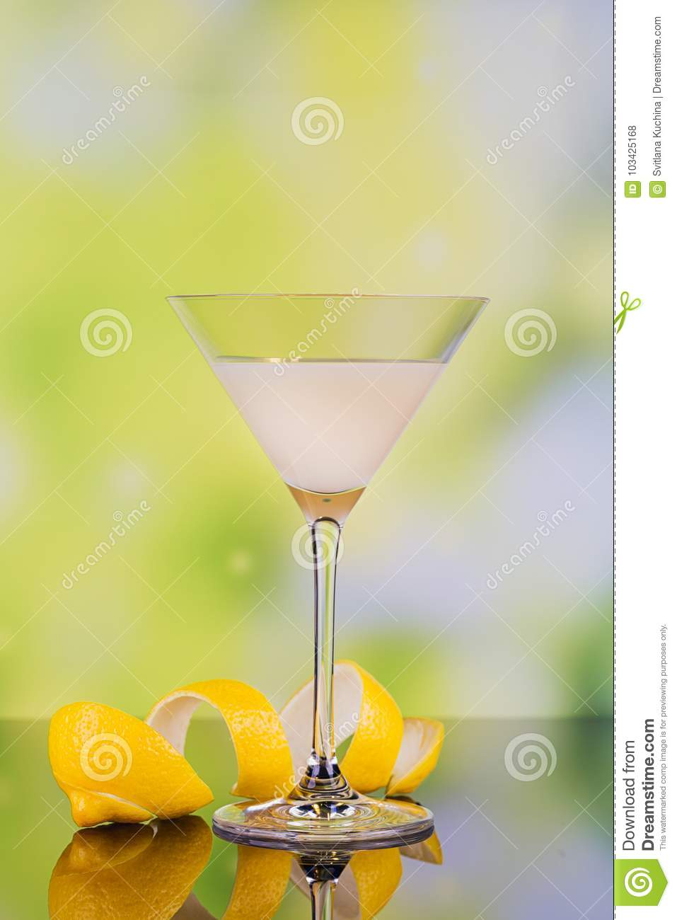 Glasses of cream liqueur with lime and lemon on green background