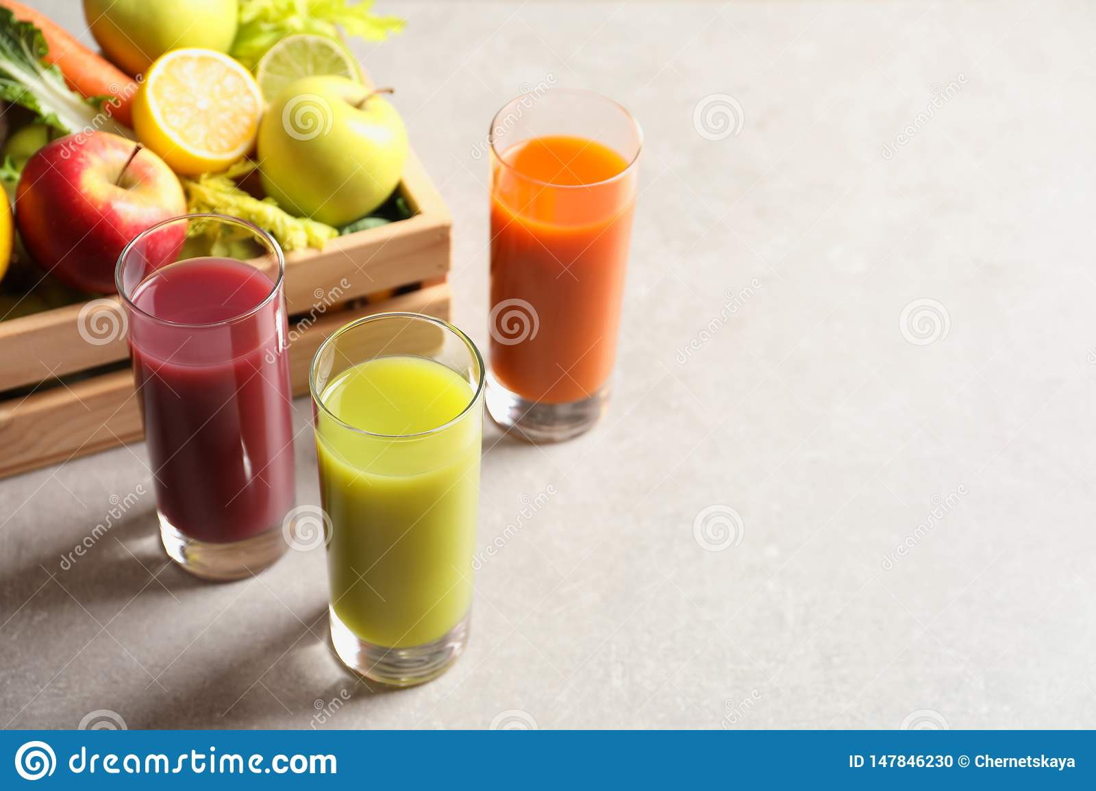 Glasses of different juices and wooden crate with fresh ingredients on table.