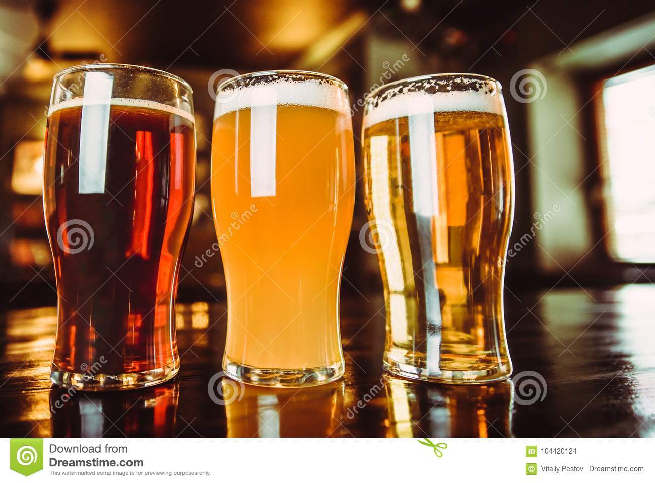 Glasses of light and dark beer on a pub background