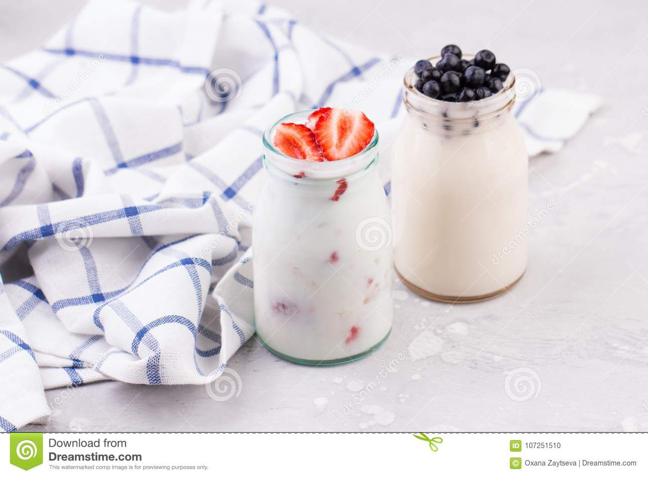 The glasses of milk shake with strawberries and blueberries on a blue checkered napkin on a white background