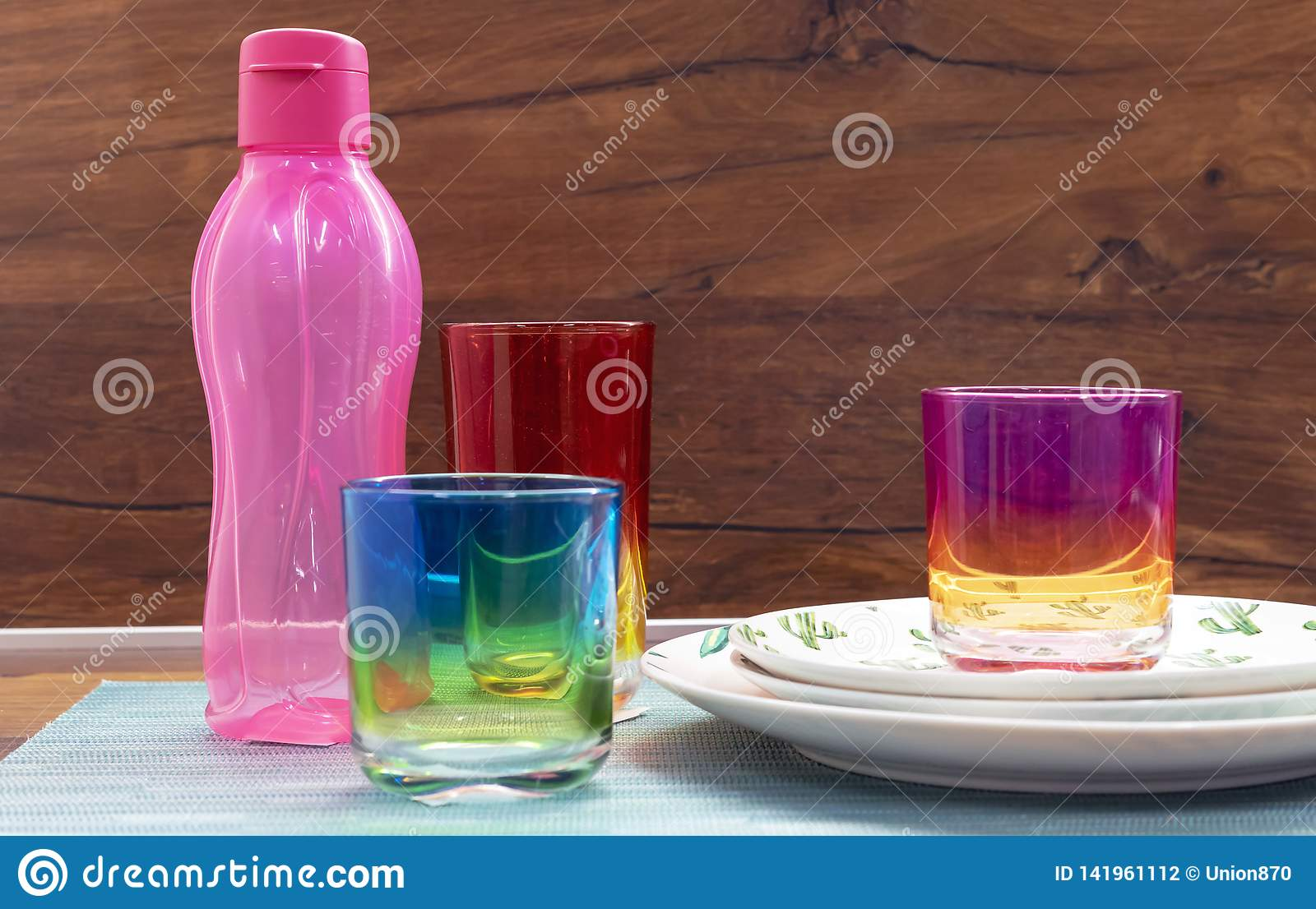 Glasses from multi-colored glass and a pink bottle for cold drinks