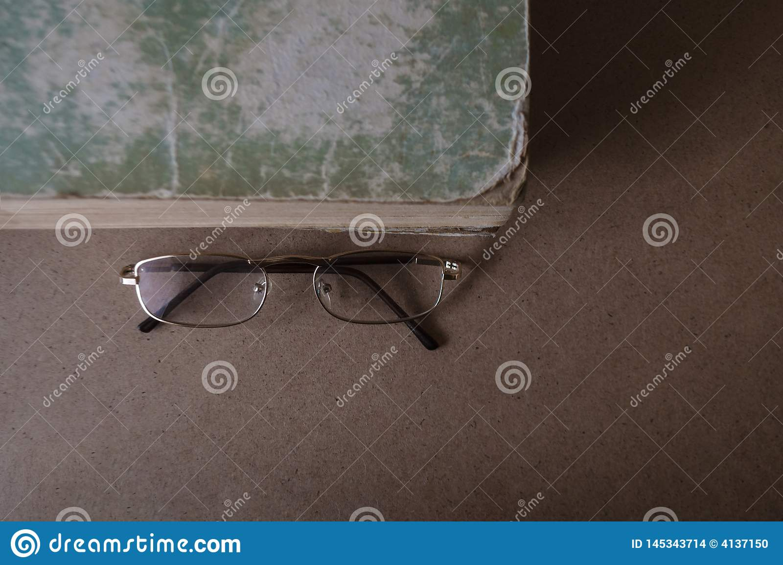 Glasses near the old book with torn edges and shabby cover. The concept of reading and education. Top view, copy space