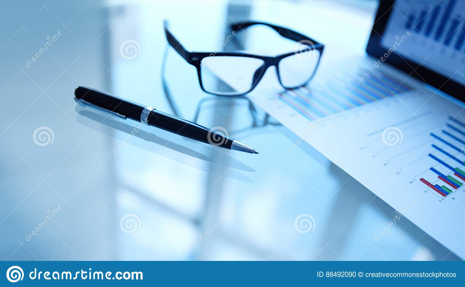 Glasses and pen next to business data