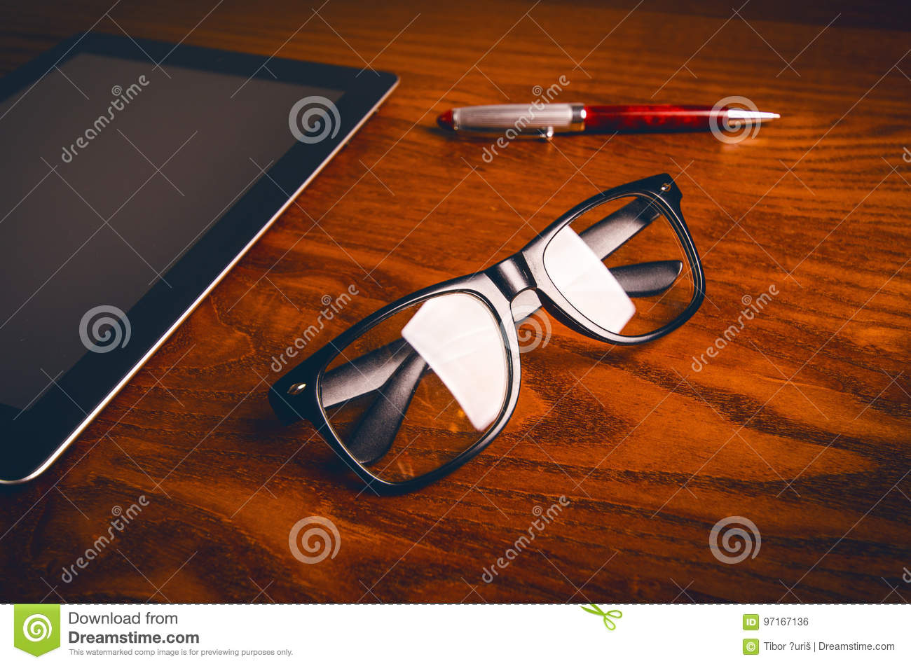 Glasses with pen and tablet on a wooden natural table. Home office. Concept of work in a office and accessories