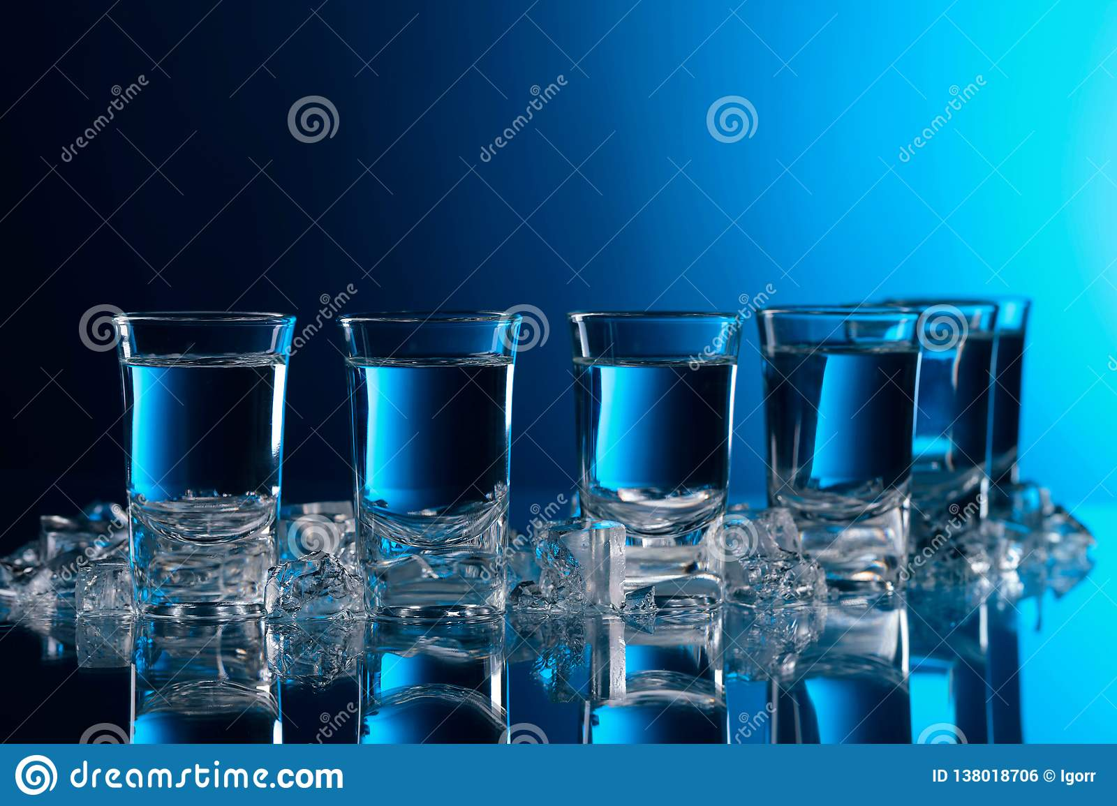 Glasses of vodka with ice on a glass table